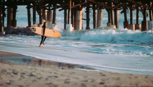Image of a surfer entering the water near Beachside Apartments in Melbourne, FL.