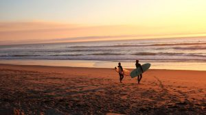 Two surfers on a beach walking towards water at sunset