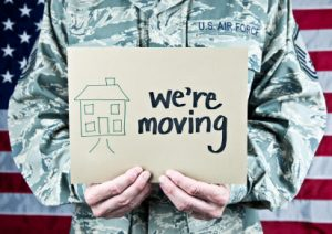 A person wearing an Air Force uniform holding a sign reading 'we're moving'