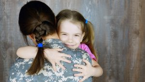 A young child hugging a woman in uniform